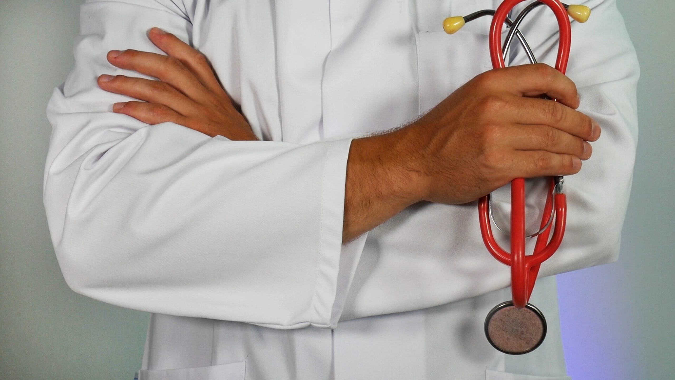 Image: a man standing with his arms cross over his chest. He is wearing a lab coat and holds a stethoscope in his hand.