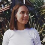 Image: Woman with brown hair, wearing a white t-shirt and earrings in the colours of the Aboriginal flag (black, yellow and red). She is looking off into space with a reflective expression on her face. In the background, there are green tropical plants.