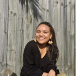 Image: Woman wearing a black jumper and gold earrings, sitting against a garden fence smiling. She has brown skin and long braids.