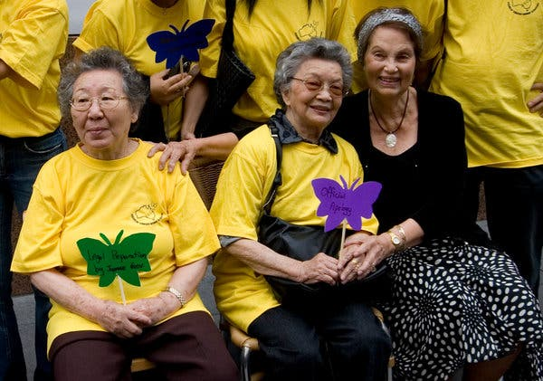[Image: a group of older women sitting together, holding paper butterflies with the message 'official apology'. Two of the women are Korean, one of the women is white.