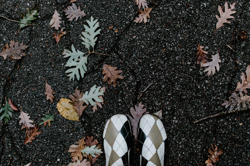 Image: woman's gum boots surrounded by autumn leaves