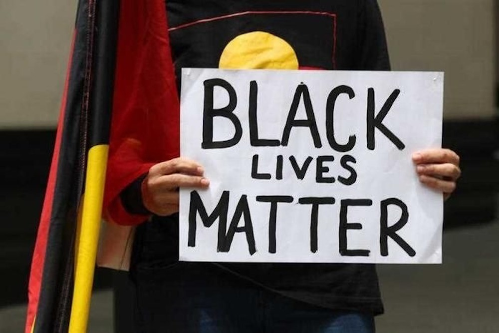 Image: photograph of a person wearing a tshirt with the Aboriginal flag across the front and an Aboriginal flag at their side, holding up a handwritten sign with the following text 'Black Lives Matter'.